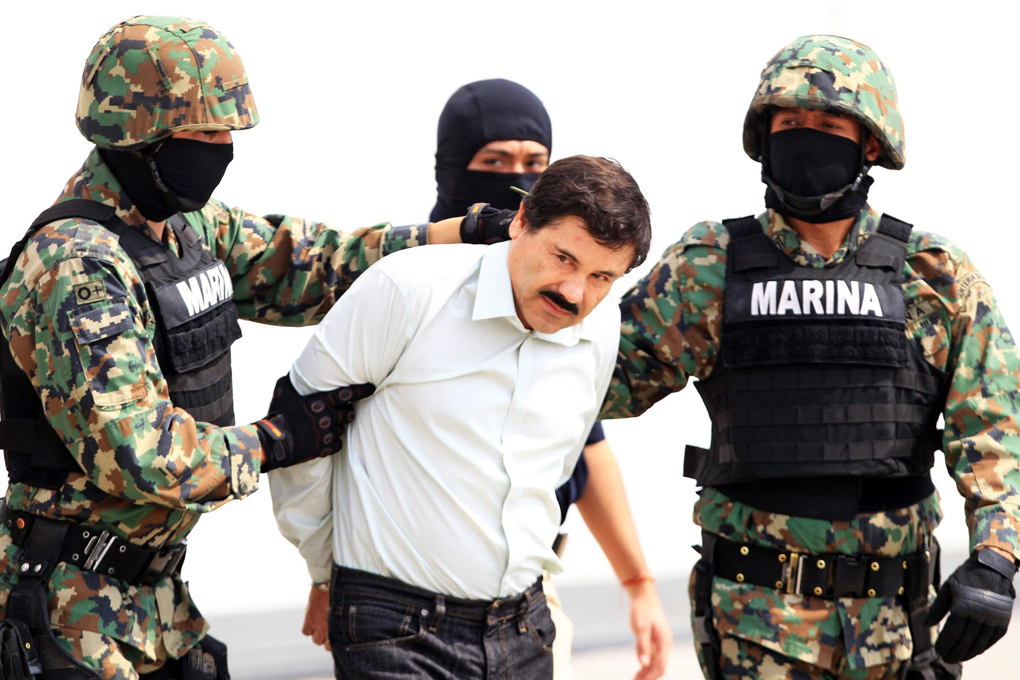 epa04096602 Mexican military hold Mexican drug lord Joaquin Guzman Loera, alias 'El Chapo' (C) at the Navy hangar in Mexico City, Mexico, 22 February 2014. The head of the Sinaloa drug cartel Joaquin 'El Chapo' Guzman was arrested on 22 February 2014 in Mazatlan in the Mexican state of Sinaloa. Reputed to be 'the most powerful drug trafficker in the world' by the United States, Guzman had been on the run for years.  EPA/MARIO GUZMAN