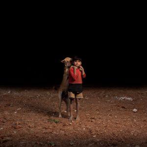 Fotografii impresionante: orfani care isi impart viata cu maidanezii…