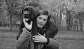 Plan de face souriant Alain DELON dans le parc de sa propriété de DOUCHY, portant sur les épaules son chien préféré, Manu, un dogue de deux mois.